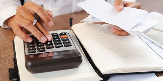 Closeup of person calculating bills on calculator. Notebook and calculator lying on desk. Accountancy concept. Cropped view.