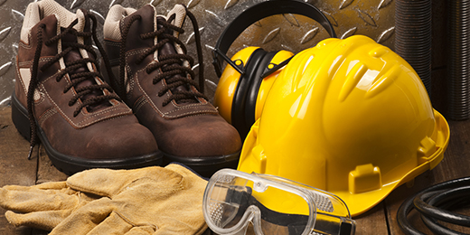 Personal Protective Workwear Shoot on Work Location. The Safety items are placed on rustic wood and includes a Yellow Hard Hat, Gloves, Steel Toe Shoes, Ear Muff and Goggles. A silver diamondplate in the background. Predominant colors are yellow and brown