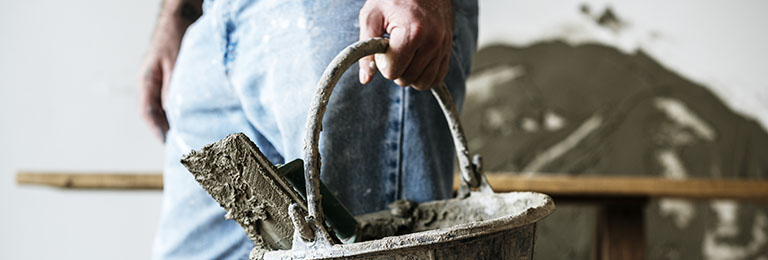 Handyman holding basket cement for construction