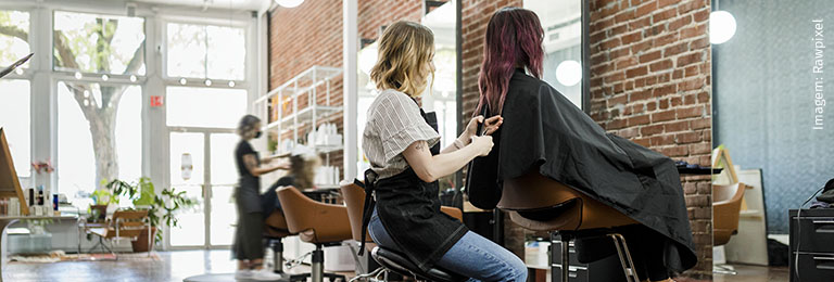 Hairstylist trimming a hair of a customer